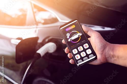 Fotografie, Obraz Using mobile smartphone device refueling electric vehicle EV car mock UI applica