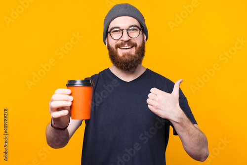 Obraz A young smilling man is enjoying his coffe and is showing a thumb up . - fototapety do salonu