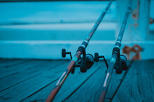 Closeup Of Dark-colored Fishing Rods On A Wooden Surface