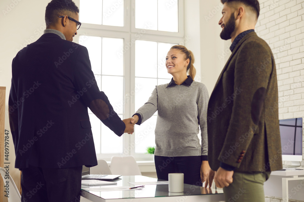 Fototapeta Happy young business people shaking hands to confirm collaboration after making successful deal in negotiation meeting in the office. Smiling company manager or bank adviser thanking client for trust