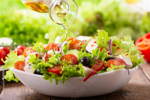 olive oil pouring into bowl of fresh salad © Nitr