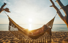 Vacation Beach Summer Holiday Concept. Young Woman Relaxing In Hammock At Sunset, Island Phu Quoc, Vietnam