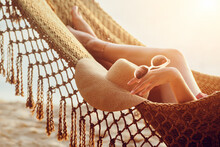 Feet And Hand Relaxing Woman In Hammock On The Beach During Sunset.