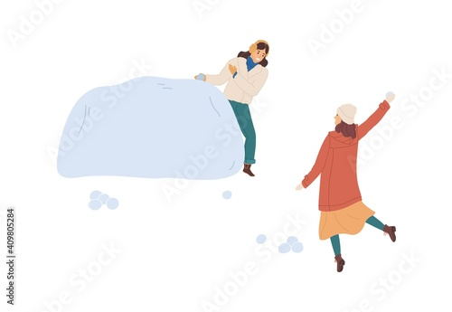 Valokuvatapetti Woman hiding behind snow fortress or snowdrift while her girlfriend throwing snowball