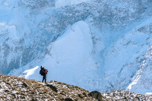 Beautiful Landscape With Mountains, Blue Huge Glacier And Silhouette Of A Man Walking With A Large Backpack And Guitar On The Background Of Mountains And Glacier