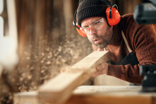 Carpenter Blowing Sawdust From Wooden Plank