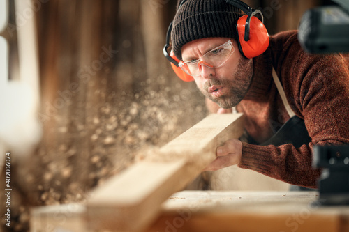 Obraz Carpenter blowing sawdust from wooden plank - fototapety do salonu
