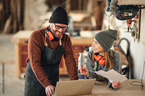 Fotografie, Obraz Cheerful joinery owners discussing project on laptop