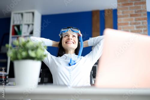 Fototapeta Woman in diving mask dreaming of sea at workplace