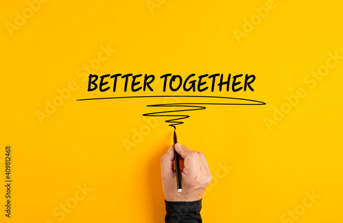 Tela Male hand writing the message better together on yellow background