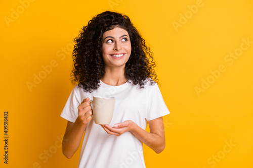 Photo portrait of curly brunette keeping cup with hot beverage looking empty space smiling isolated on vibrant yellow color background © deagreez
