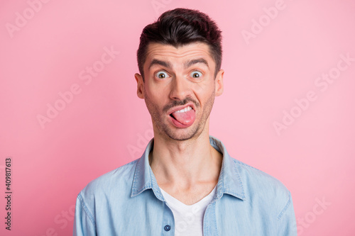Fototapeta Photo portrait of silly crazy tricky guy showing tongue grimacing isolated pastel pink color background obraz na płótnie