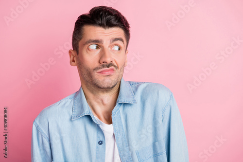 Fototapeta Photo of confused brunette handsome young man wear blue shirt isolated on pastel pink color background obraz na płótnie