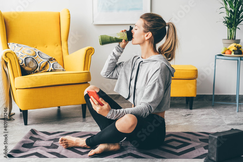 Obraz na plátne Beautiful woman drinking smoothie to refresh after workout.