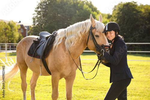 Fotografija Young woman in horse riding suit and her beautiful pet outdoors on sunny day