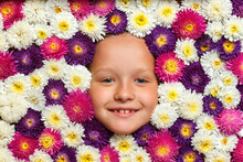 Cheerful Cute Face Of A Little Girl In Flowers Aster Colors Of White, Purple, Pink. Top View Of The Child.
