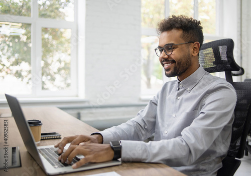 Fotografie, Obraz Confident businessman working on laptop at his workplace at modern office, Young