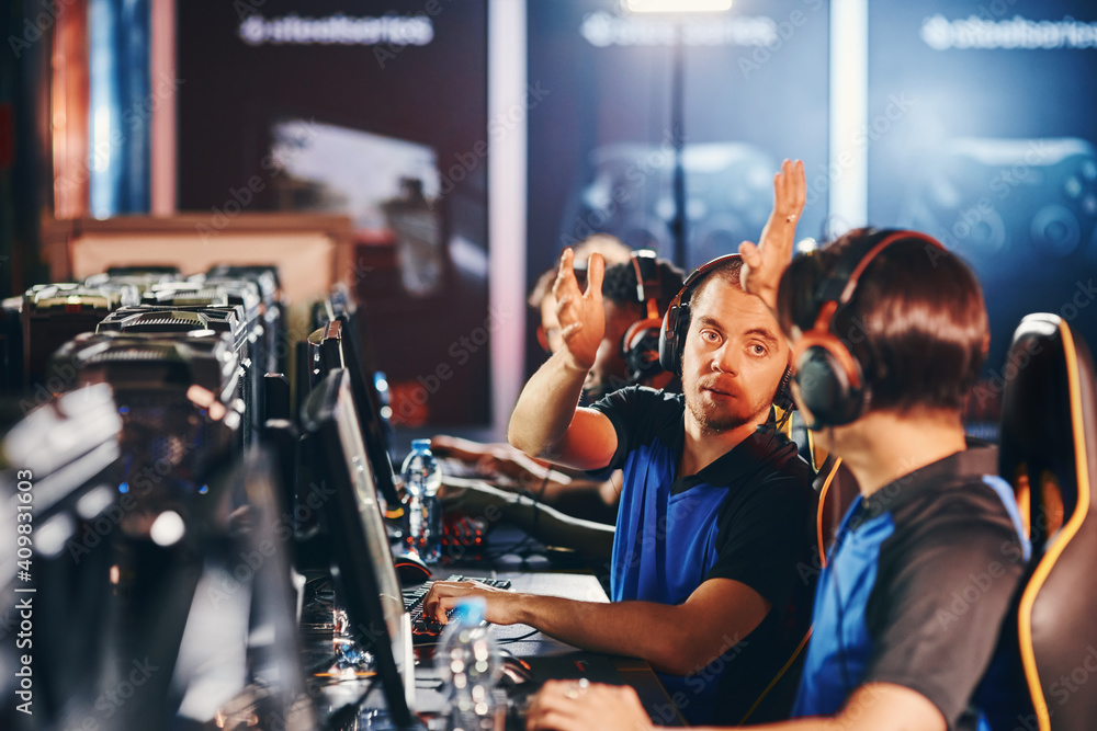 Fototapeta We are winning. Two happy male cyber sport gamers giving high five to each other, celebrating success while participating as one team in eSports tournament