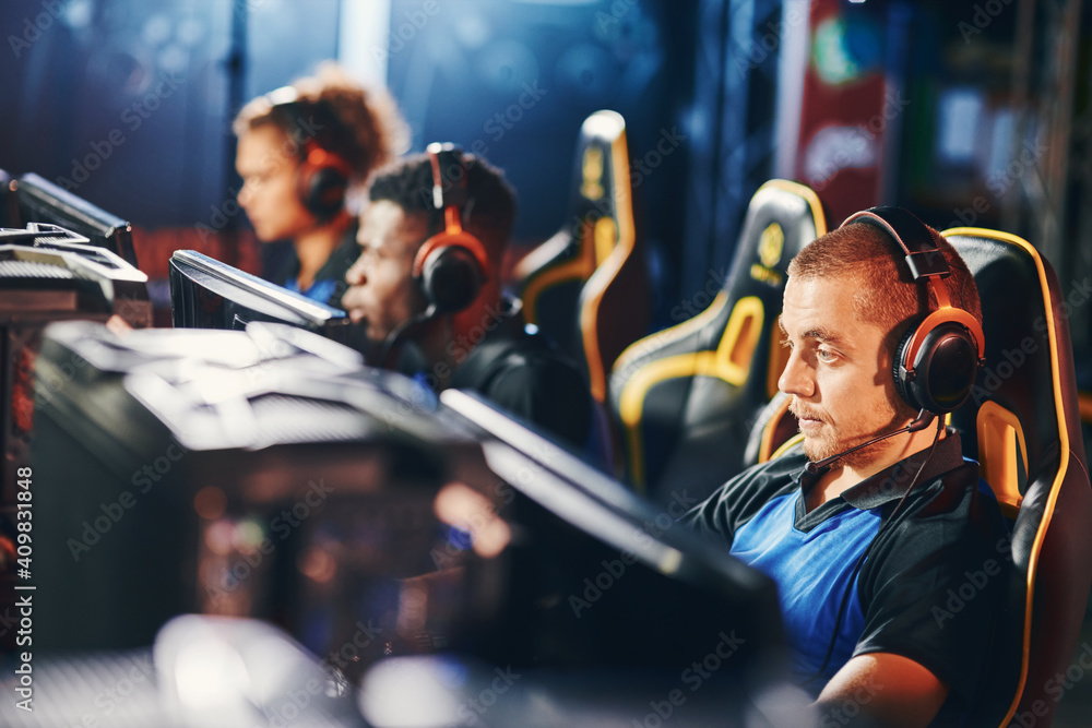 Fototapeta Focused on game. Male cybersport gamer wearing headphones playing online video games, participating in eSport tournament