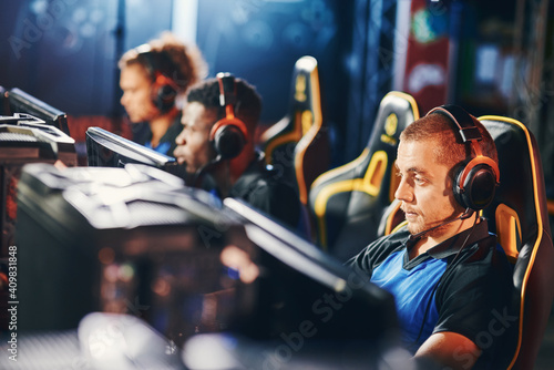 Obraz Focused on game. Male cybersport gamer wearing headphones playing online video games, participating in eSport tournament - fototapety do salonu
