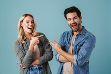 Young Excited Man And Woman Pointing Fingers At Each Other