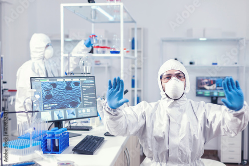 Valokuvatapetti Healthcare engineer in laboratory looking at digital screen holding hands up
