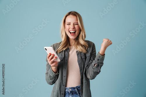 Valokuvatapetti Delighted blonde girl making winner gesture and using mobile phone