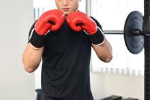 ボクシンググローブをつけてパンチを打つ若い男性