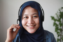 Beautiful Asian Muslim Woman Using Headphones Speaking To Camera, Explaining Something. Professional Teacher Mentor Customer Service Support Doing Online Chat Or Video Call