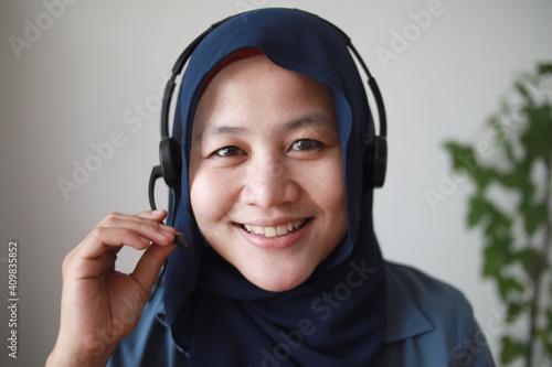 Beautiful Asian muslim woman using headphones speaking to camera, explaining something Wallpaper Mural