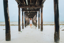 Portrait Of A Happy Cheerful Smiling Woman Dressed In Light Summer Clothes Walking Barefoot Under The Sandy Beach Wooden Pier. Careless Vacation In The Tropical Countries Concept Image