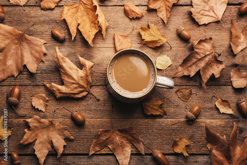 Fototapeta Cup of hot drink and autumn leaves on wooden table, flat lay. Cozy atmosphere obraz
