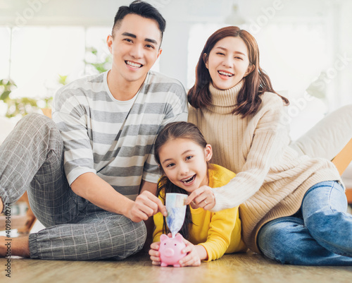 Father, mother and daughter holding a piggy bank and money  at home Fotobehang