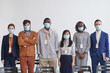 Leinwandbild Motiv Multi-ethnic group of business people wearing masks and looking at camera while standing in row against white in conference room