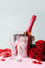 Sparkling Wine, Gift, Red Roses And Chocolate Sweets For Valentine's Day On Blue. Vertical Greeting Card.