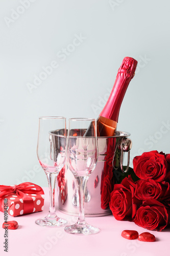 Sparkling wine, gift, red roses and chocolate sweets for Valentine's day on blue. Vertical greeting card. © svetlana_cherruty