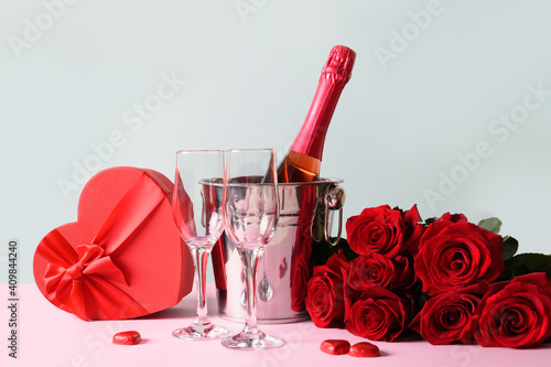 Valentine's day heart gift greeting card with gift and red sparkling wine on blue. Banner with copy space. © svetlana_cherruty