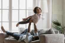 African American Father Holding Little Son Pretending Flying, Having Fun, Lying On Cozy Couch At Home, Excited Cute Boy With Dad Involved In Funny Activity, Spending Leisure Time Together