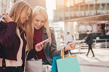 Happy Girlfriends With Shopping Bags Using Smartphone In City