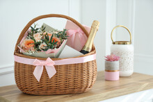 Wicker Basket With Gifts On Table Indoors