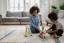 Happy African American Boy And Girl Playing With Toy Dinosaurs And Wooden Blocks Cubes In Living Room, Sitting On Warm Floor With Underfloor Heating, Little Siblings Having Fun At Home Together