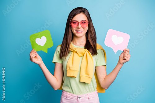 Obraz Photo of young lovely pretty attractive happy smiling girl in funky glasses hold heart icons isolated on blue color background - fototapety do salonu