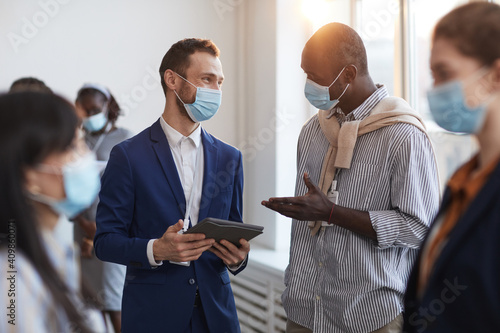 Obraz Waist up portrait of group of people chatting during break at business conference, focus on two men wearing masks with lens flare - fototapety do salonu