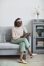 Vertical Full Length Portrait Of Young African-American Woman Using Digital Tablet While Sitting On Sofa At Home In Minimal Grey Interior, Copy Space