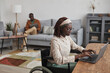 Portrait of young African-American woman using wheelchair while working from home in minimal grey interior, copy space