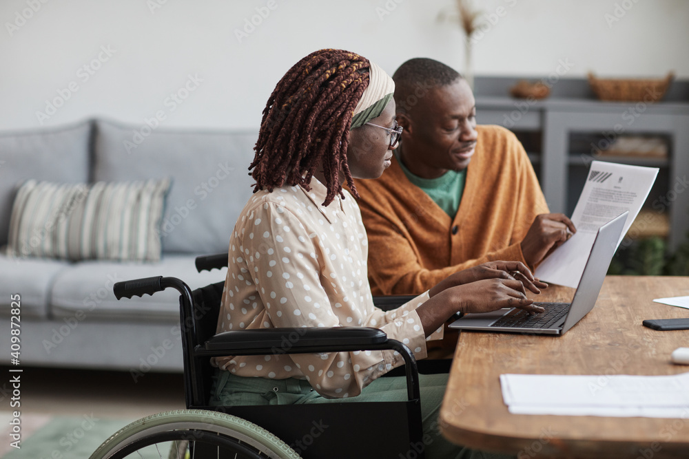 Fototapeta Side view portrait of young African-American woman using wheelchair working from home with husband helping her copy space