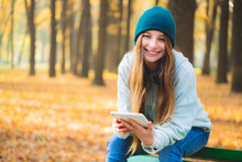 Smiling Girl On Bench With Tablet In Autumn Park