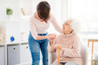 canvas print picture - Kind woman helping lovely old lady to stand from chair