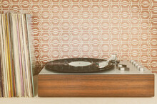 Vintage Record Player With Record Albums In Front Of Seventies Wallpaper