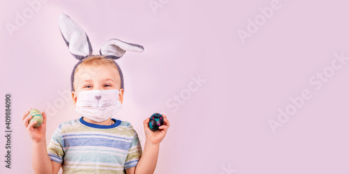 Slika na platnu Cute baby boy in rabbit bunny ears on head and protective mask with colored eggs on pink background
